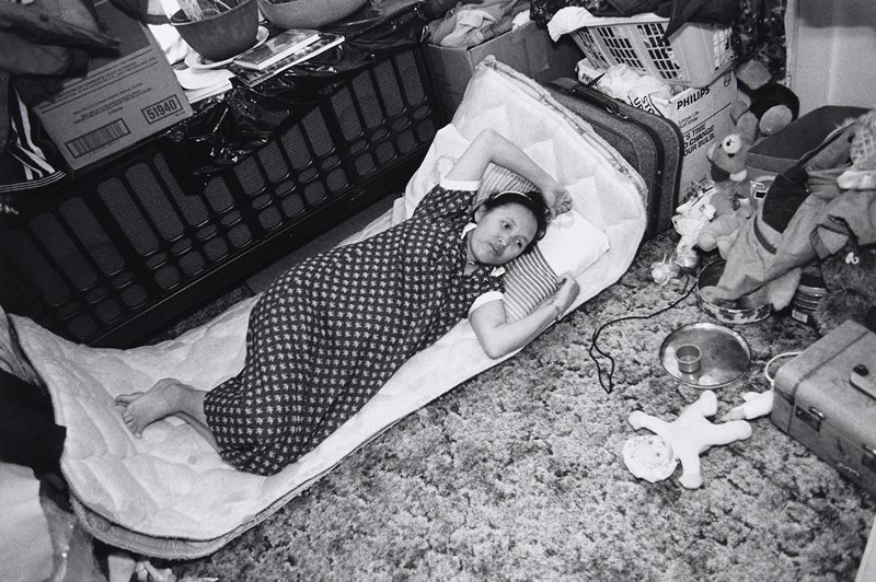 black and white photo of woman lying on mat on floor surrounded by boxes and toys