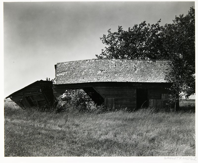 old barn with missing shingles; partially collapsed shed attached to left end of barn