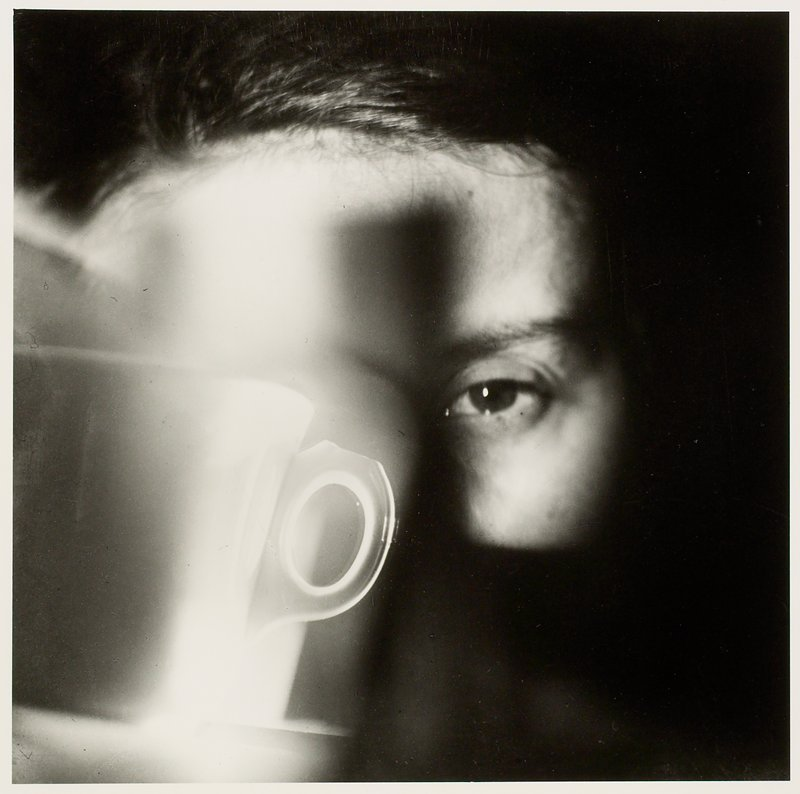 glowing coffee cup lower left corner; woman's face behind cup (only forehead and proper left eye visible)