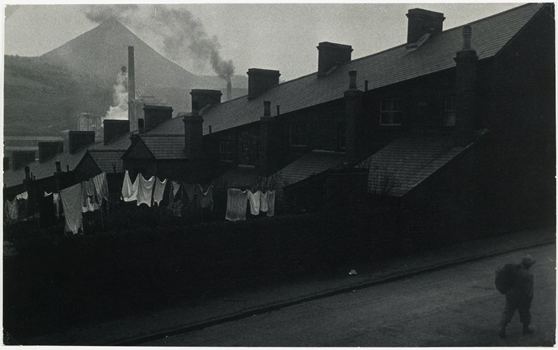 Row house with chimneys and laundry hanging outside; man with a bag over in shoulder, walking on road, lower right corner