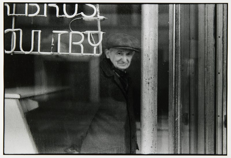 man with hat looking out of window on rainy day