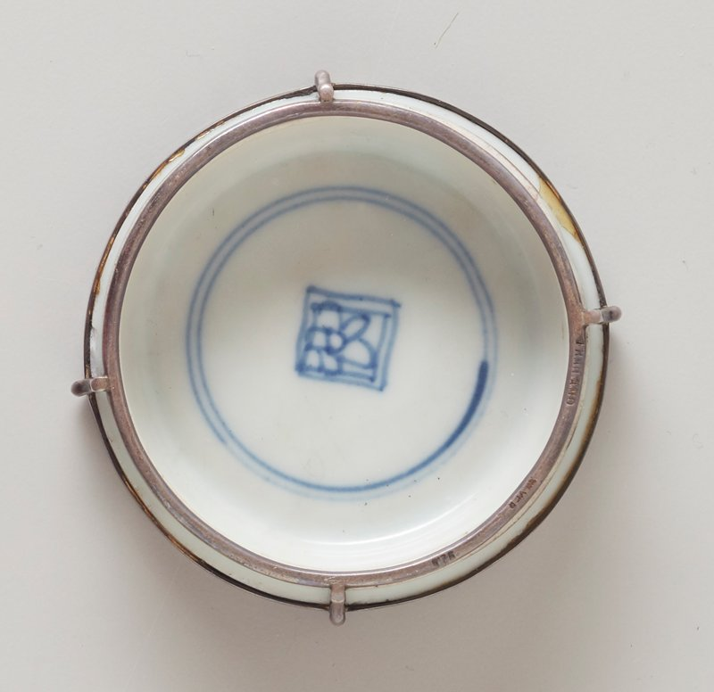 Small bowl with silver fittings at top rim and bottom edge, with four vertical elements at edges; glazed white with two concentric circles and floral design inside a square at interior and stylized landscape forms (water and foliage) on bottom, all in blue