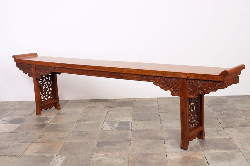Very long table with apron on all four sides with carved clouds and geometric designs; two support legs near short ends with openwork dragons inside geometric framework; short ends of table raised and curved