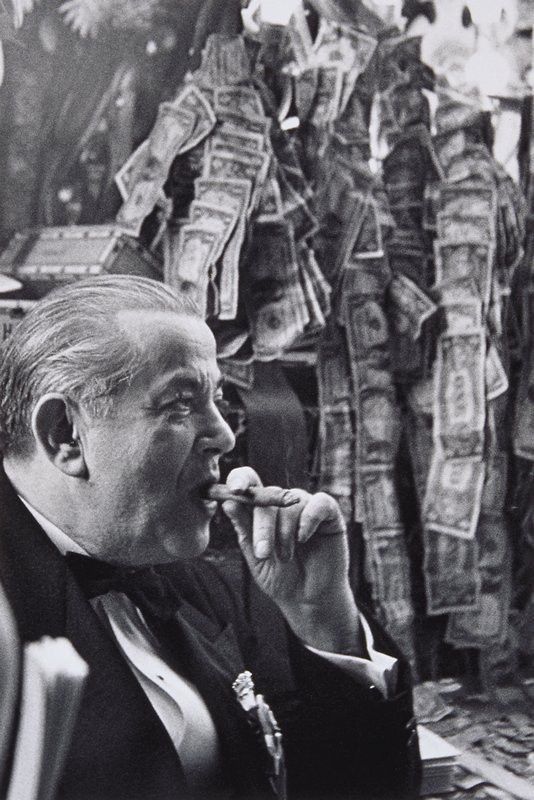 middle-aged, heavy set man wearing a tuxedo and smoking a cigar, seen from the chest up; dollar bills attached together in hanging ribbons in background