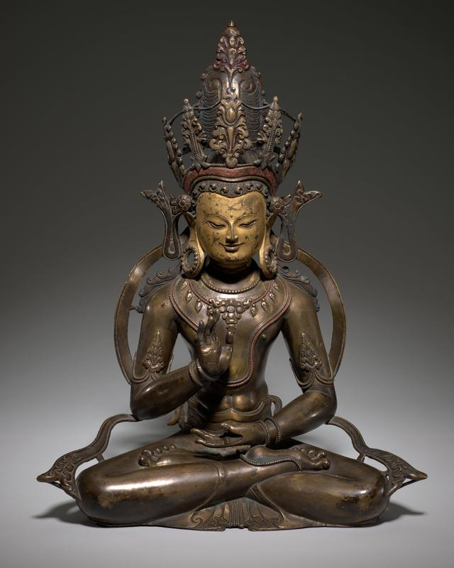 Cross-legged seated man with PL hand palm up on lap and PR hand raised to chest level; wearing elaborate headgear and jewelry with elongated pierced ears; has own mount