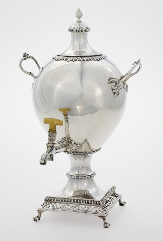 silver hot water urn; small clawed feet, square base with scrolling open work, rope banding, owl with crown at front top of base and cover (opposite a crest), egg shaped body, leaf handle attachments, spiraling flame at top center of cover, longstemed spout with ivory 'T' handle