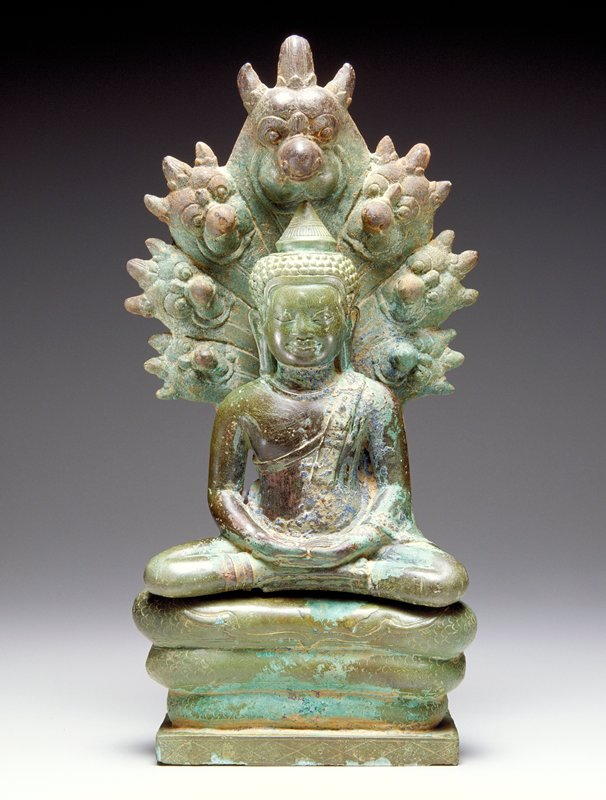 seated Buddha with hands on lap; small pointed hat on top of head; coiled snake body throne; 7 doglike heads on back of throne; smiling expression