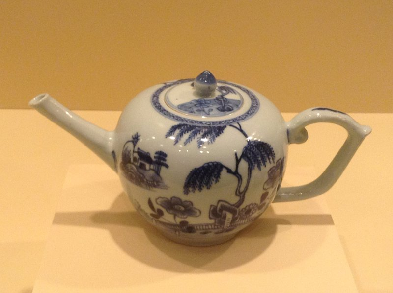 Chinese Export blue and white porcelain; bullet-shaped form; painted with willow and peony; a terrace on a rock with a scholar's retreat; trellis pattern borders