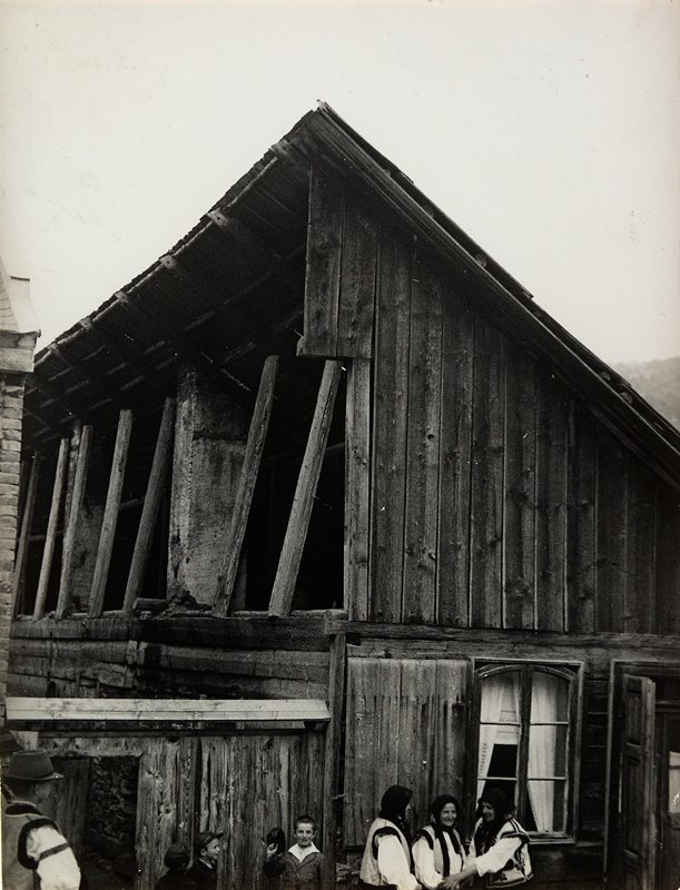 building with sloped roof and open loft-like 2nd floor, seen from exterior; 3 women wearing vests and scarves at LR and 4 young men at LL
