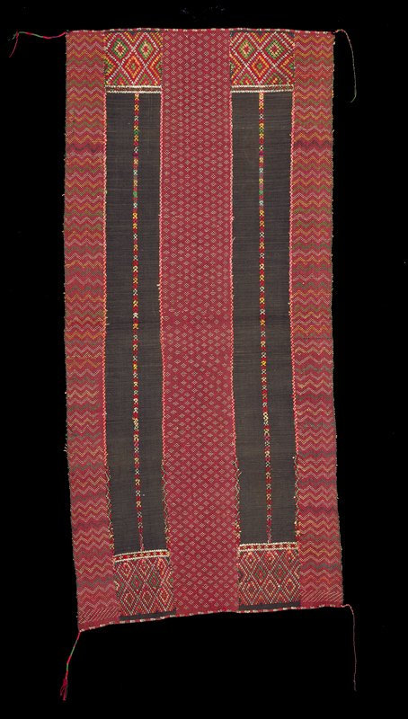 weave type (?) red ground with multi-colored patterning (zig-zags at outside edges and lozenge at center); 2 vertical brown bands; braided cords at 4 corners