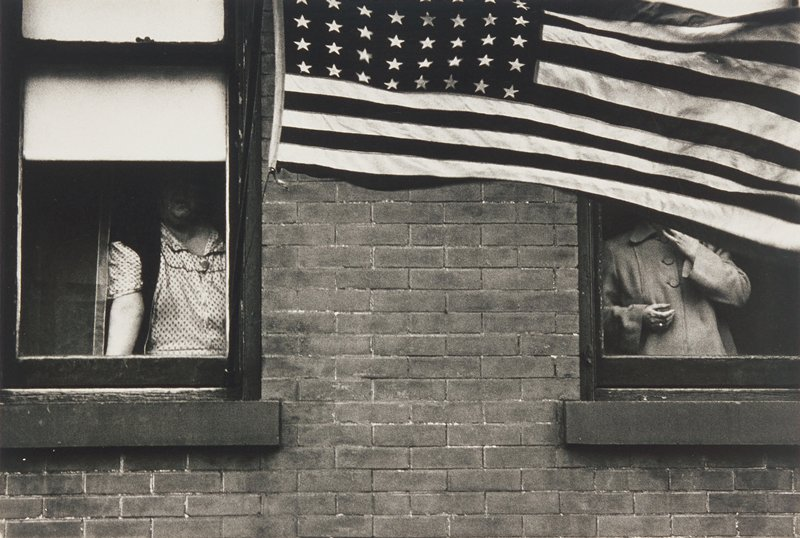 people standing at windows, American flag across window on right