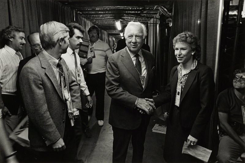 Walter Cronkite, center, shaking hands with woman, right