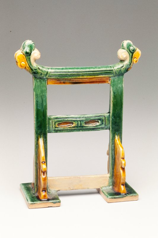 Tomb furniture; stand for a screen with 2 vertical elements, resting on small platforms, and three horizontal elements, the topmost decorated with an organic, flowerlike design at the ends; glazed green and tan