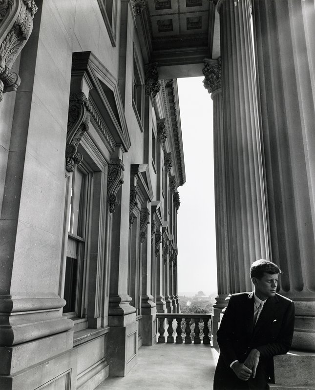 man wearing suit, leaning against column in LRC of image