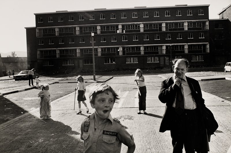 boy in sheriff shirt center foreground; five story building in background; man and young children in the square
