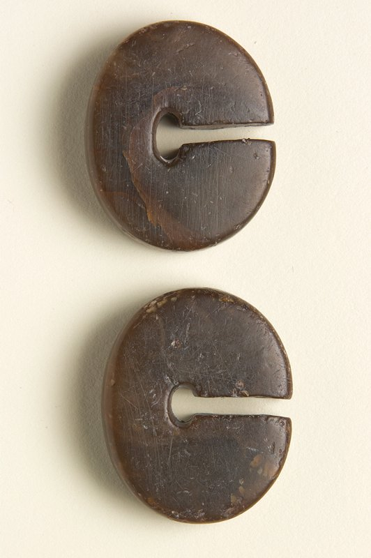 2 oval-shaped discs with flat sides; slightly wider at bottom; brown stone with dark and light streaks