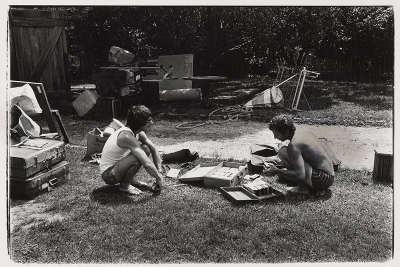 2 crouching men man at L wears tank top, shorts, thongs and sunglasses; man at R wears shorts and holds a stack of cassette tapes, with 2 cases of tapes on the ground in front of him; suitcases, boxes and other objects scattered throughout