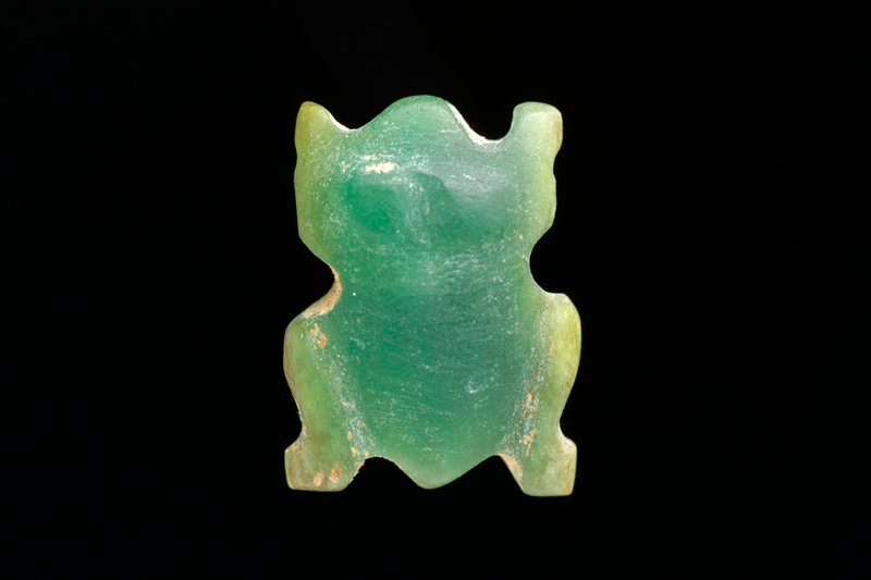 green stone carved in the shape of a frog; horizontal hole through side of body (partially encrusted with tan accretions)