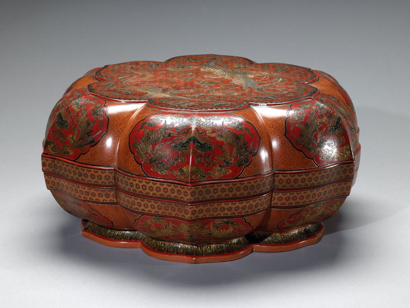 hexagonal Box with lid, red lacquer. Flat top incised with two phoenix in flight among flowering peonies on a cell pattern ground; sides with shaped reserves of confronting dragons on key fret ground. Qianlong six character mark.