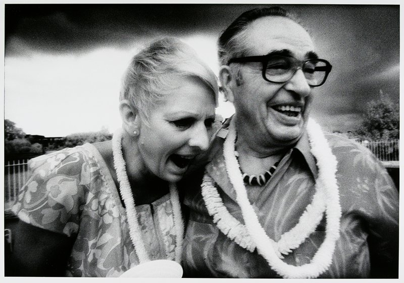 woman wearing flowered blouse and lei, with short blonde hair, leaning against a man wearing heavy glasses, a Hawaiian shirt and 2 lei's