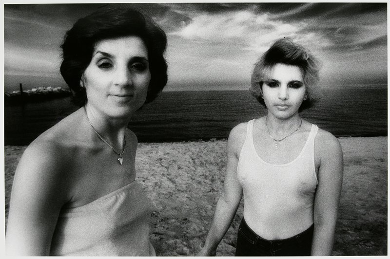 2 women standing in front of water; woman at L has dark hair and wears a necklace and strapless shirt; woman at R has light hair and heavily made-up eyes and wears a form-fitting tank top and necklace; matted