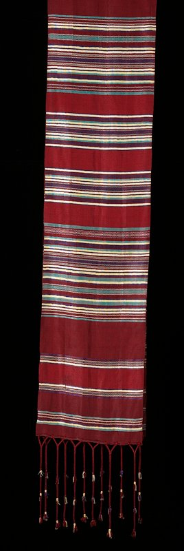 twill weave; rust red central portion and ground with tan, purple and green zigzags and stripes; braided tassels with yellow and purple thread trim and sequins