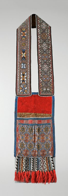 bag with wide shoulder strap with beaded geometric designs; back of strap and interior of bag printed brown fabric; front panel of bag beaded with geometric shapes; top panel and back of bag red wool; 17 short beaded hanging tails with red wool tassels; body of bag trimmed in blue
