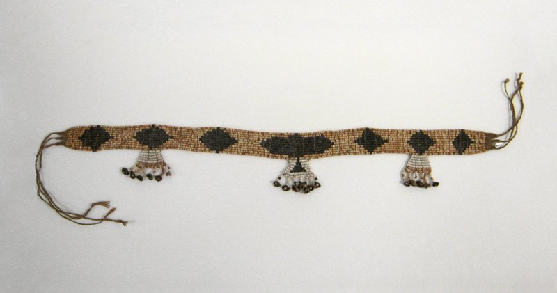 belt made of shells threaded onto cords and tied together; band consists of 3 dark brown diamonds to R and L of a dark brown oval; 3 hanging pendants with bead tassels