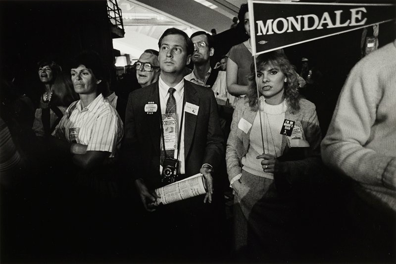 man, left, with camera around his neck holding a paper next to woman, right, holding 'Mondale' pennant