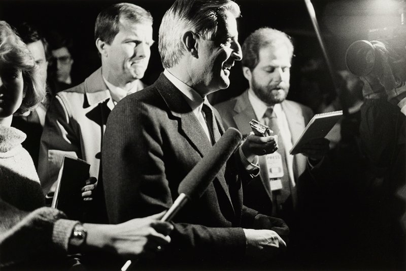 Walter Mondale, facing right, surrounded by reporters; microphone being held in front