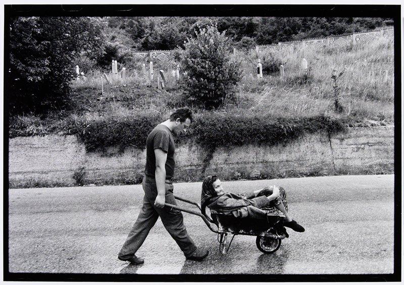 man pushing older woman in a wheelbarrow
