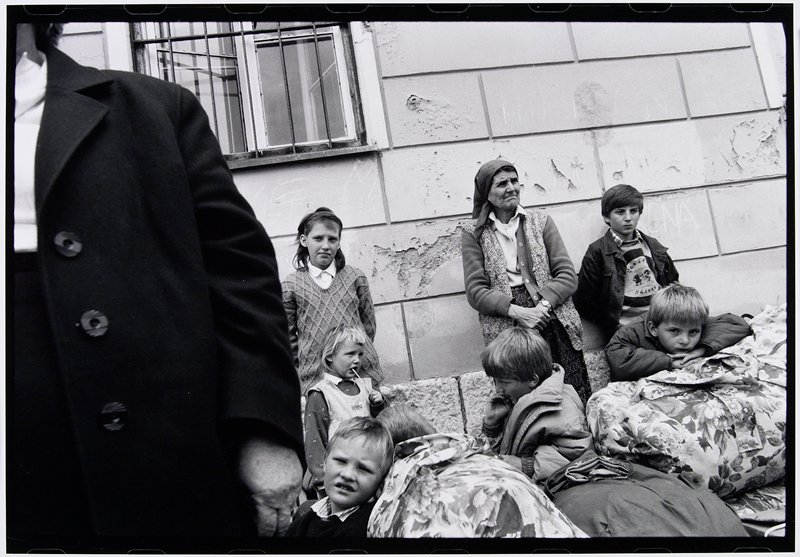 older woman and six children in front of exterior wall