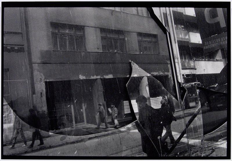 people walking on streets seen reflected on broken glass