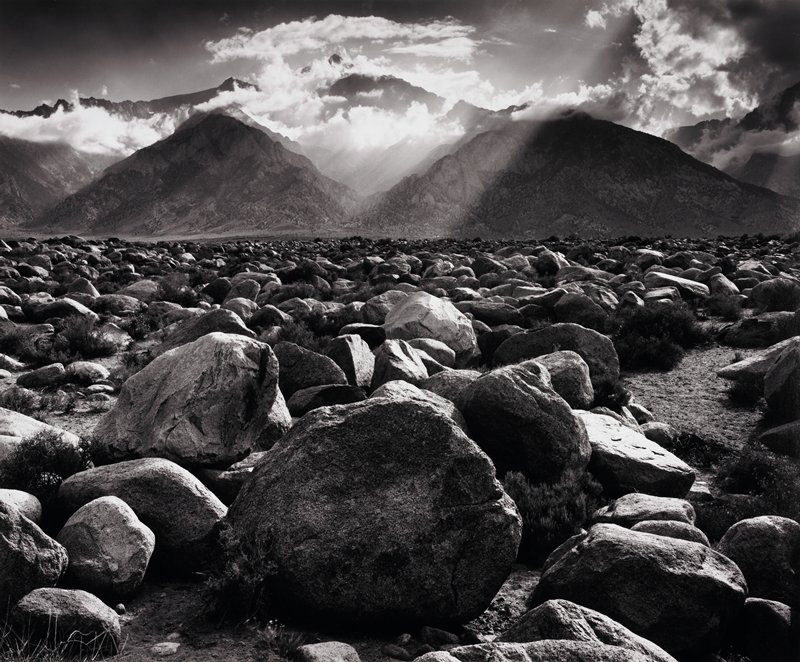large boulders in foreground; mountains and clouds in the background