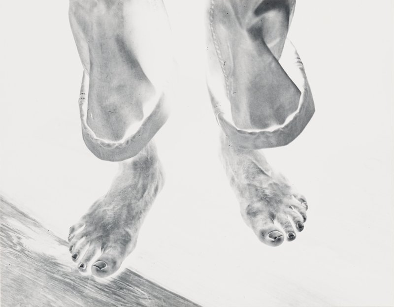 negative image of man's feet, wearing rolled-up pants