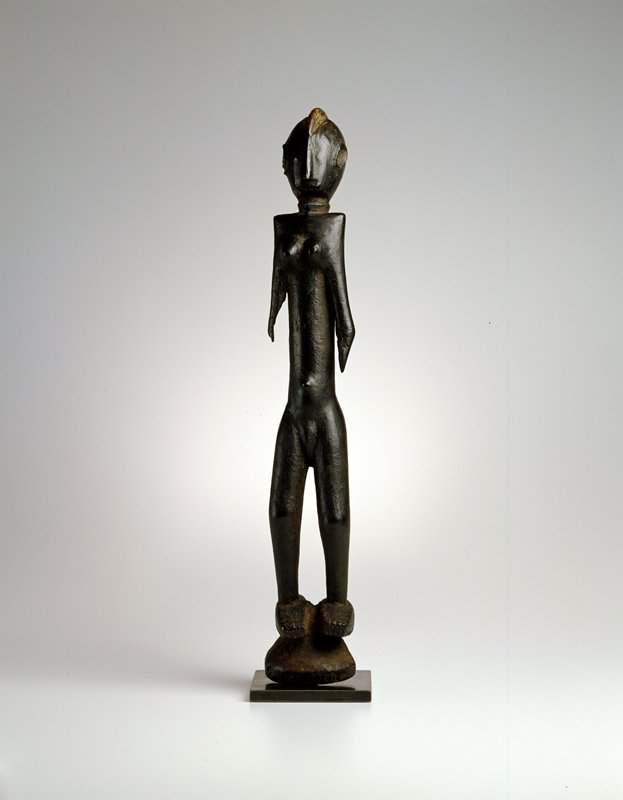standing female figure; wood; from a 'Karan-Wemba' mask, with heavy encrustation and showing faint lines of body scarification, wood (type unknown)