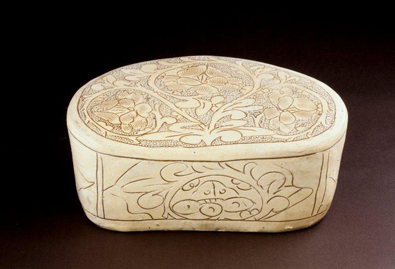 Tz'u-chou pillow, bean-shaped with leaf design, incised against punch-mark ground on white slip coating; stoneware.