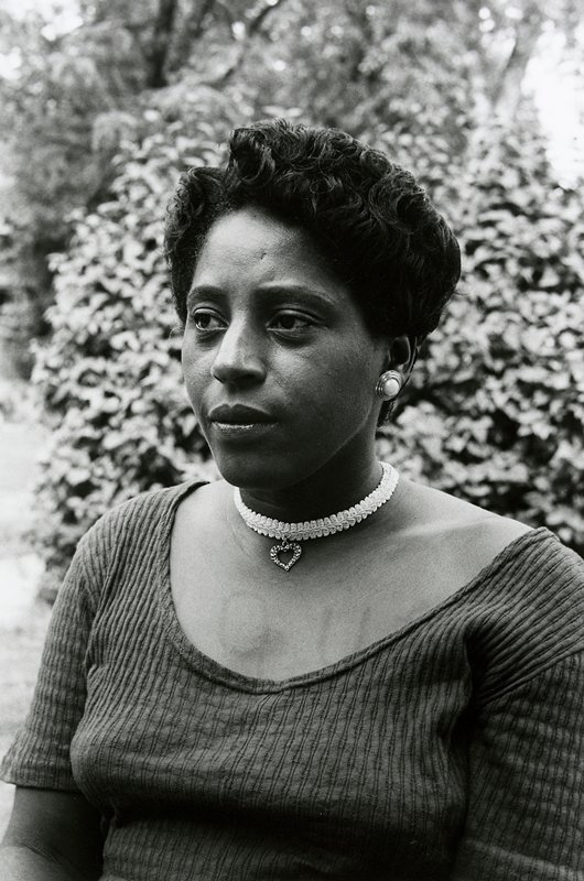 black and white photo of woman with letters tatooed on chest; looking away from camera; wearing choker with heart pendant