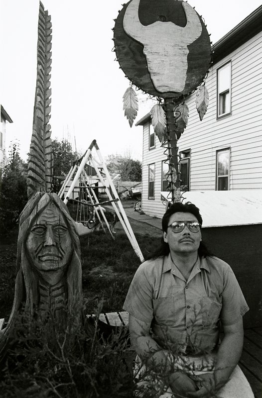 black and white photo of man looking up at sky, seated next to statue of Native American; swingset in background