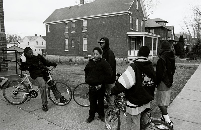 black and white photo of five teenagers on sidewalk; three bikes