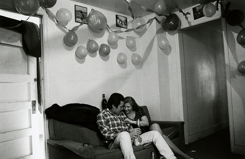 black and white photo of man and woman on couch, balloons on ceiling