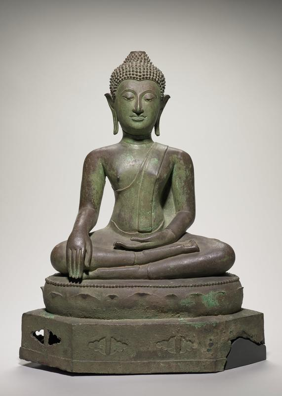 Buddha, bronze seated figure in attitude of contemplation, also known as the Mudra, or position of 'calling the earth to witness'. The green bronze pedestal is in two tiers; the upper one shows lotus leaves in relief beneath a beaded rim, and the lower, (broken at right side) with ovoid indentations, some of them perforated. The ears are weighted but unadorned. The hair is short, in spiky curls and the usnisa had indentation to hold flame, which is missing. The eyes are enameled, proving the figure to be a late piece.