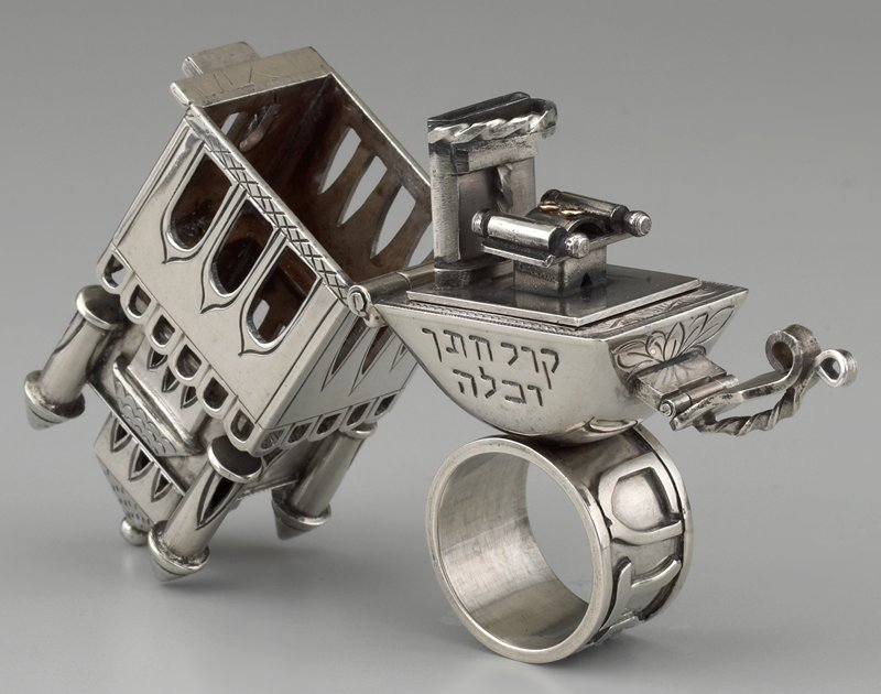 building form attached to ring; open windows on 3-level building; building opens to reveal removable torah and altar (?) on a platform; has plexi mount