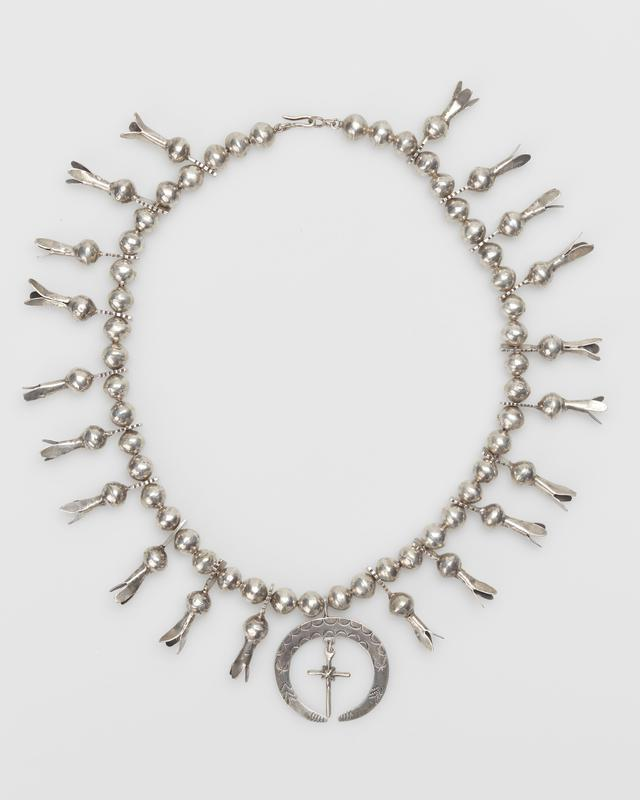 Single strand of large silver beads; 10 large 3-pronged squash blossoms (on ea. side) with pierced extensions filed on one side; stamped hammered naja, cast pendant cross; silver chain and silver clasp. J.#434, Cat.#390.