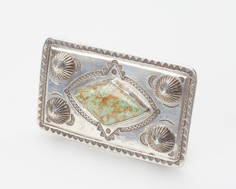 Square silver with diamond shaped turquoise in center; 4 silver buttons; stamped designs; made for modern belt; stamped G.N.M. on back. J.#564, Cat.#(none).