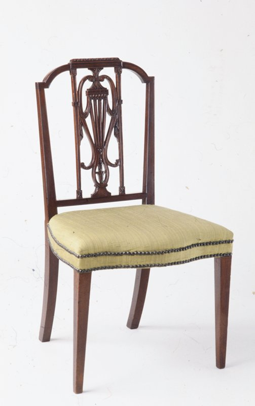 side chair; style of Sheraton; pierced splat, below a curved crest rail, displays variation and combination of urn and lyre motifs and drapery swags enclosed within narrow, tapering uprights, the whole surmounted by carved cresting; seat, serpentine front, upholstered in green satin; straight, square tapering legs