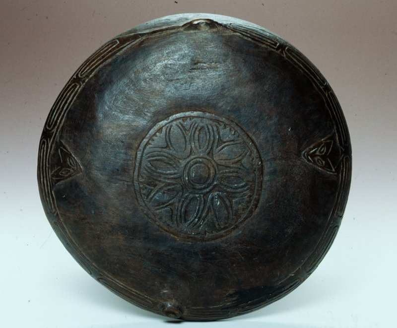 Round shallow bowl. Brown in color with a floral design carved into bottom. Incised design around rim.