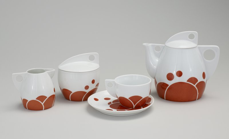 cup and saucer with red-orange circular and semi-circular decoration on white ground; part of tea service which includes teapot (L99.227.7.1a,b), covered sugar bowl and creamer (L99.227.7.3-4 ), Norwest #87-4(teapot); 88-28 (sugar bowl & creamer)