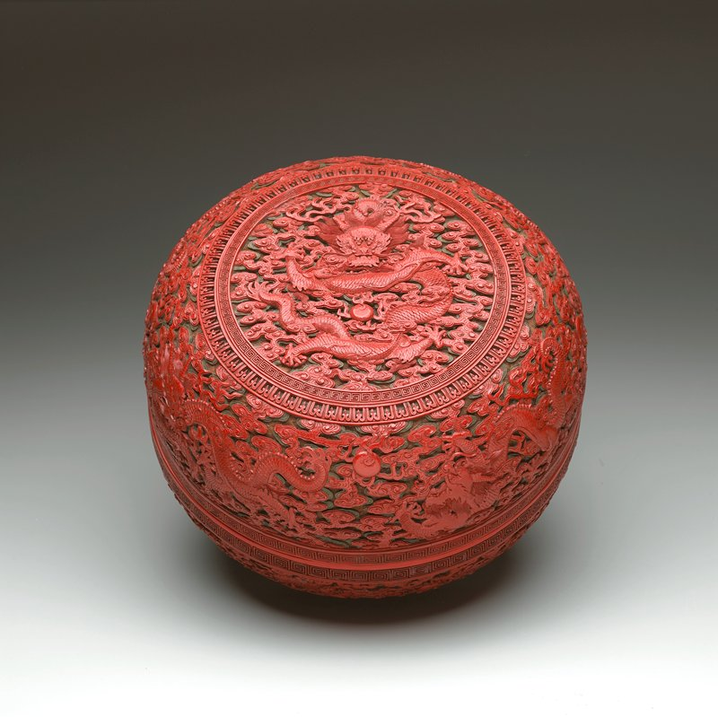 rounded box on a short foot; carved red, green and brown lacquer; dragons in cloud forms around base and cover with dragon at top; geometric bands