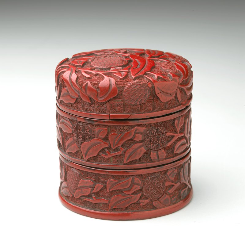 cylindrical form with slightly domed cover; carved overall with lychee against a patterned ground